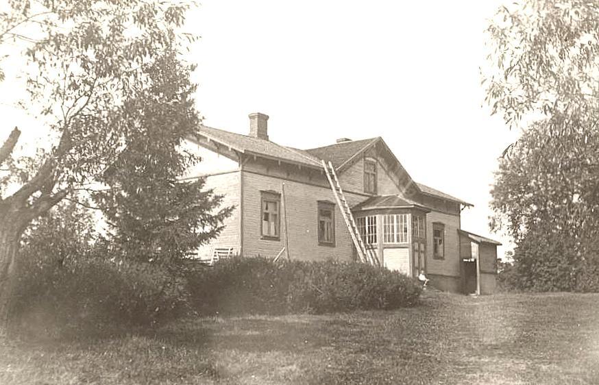 Kuhmalahden pappila v. 1920. Kyseisessä rakennuksessa sukuseuran perinnehenkilö Herman Liikanen kuoli 13.4.1926 huoneessa, joka on talon vasemmassa päädyssä ensimmäisen ikkunan takana. Kuva Pekka Saarenmaan albumista.   Silloin kirkkoherrana oli Hermanin sisaren poika Knut Saarenmaa.  Rakennuksen seinään kiinnitettiin 23.7.2004 asiasta kertova muistoreliefi.